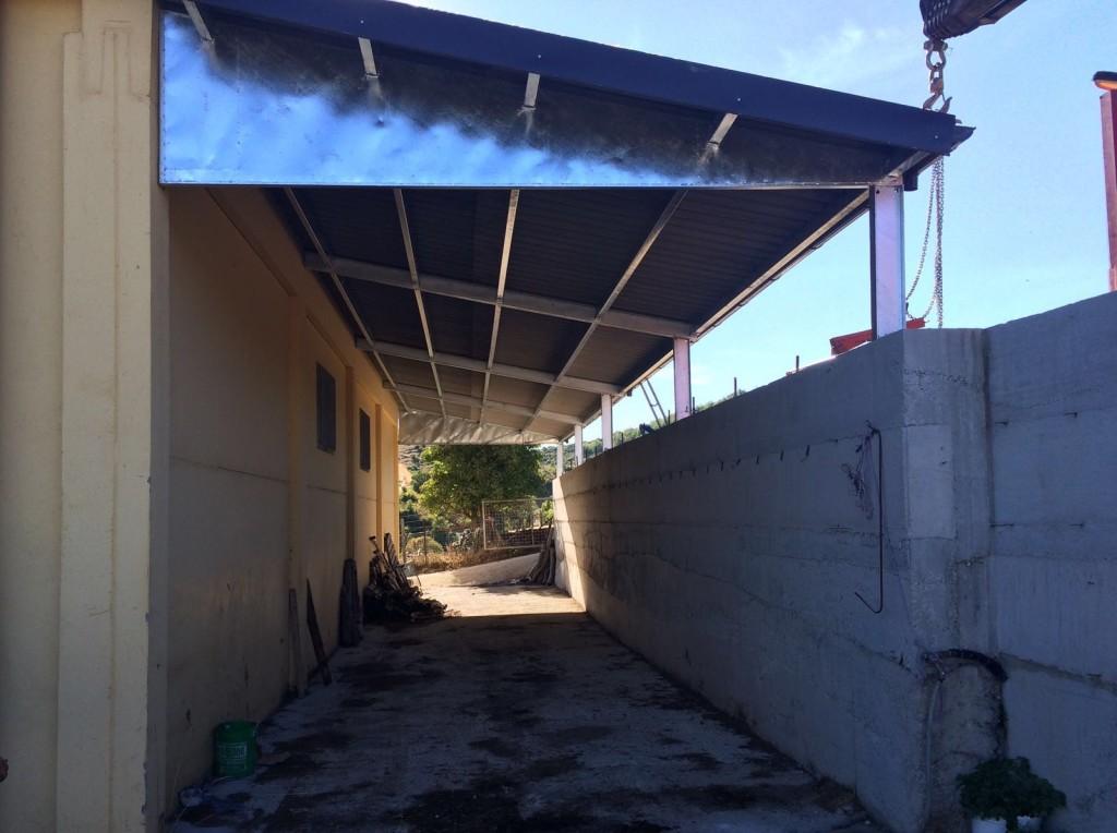 vista di una capriata in ferro zincato di una tettoia ancorata su un capannone